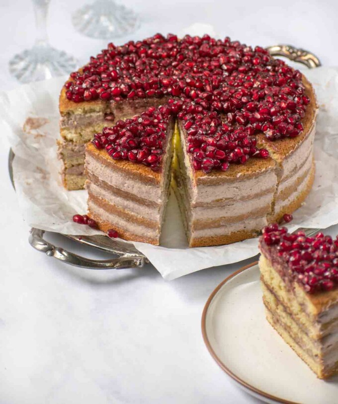 whole pomegranate mousse cake sliced with slice out on a plate in the foreground