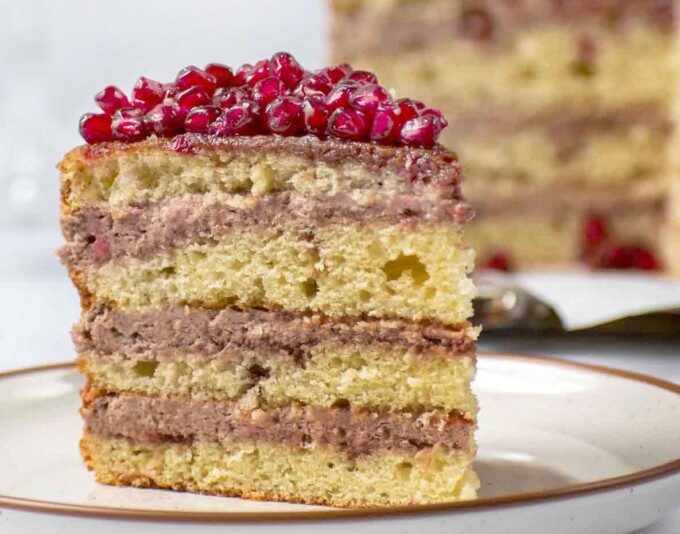 slice of pomegranate mousse cake with whole cake in the background