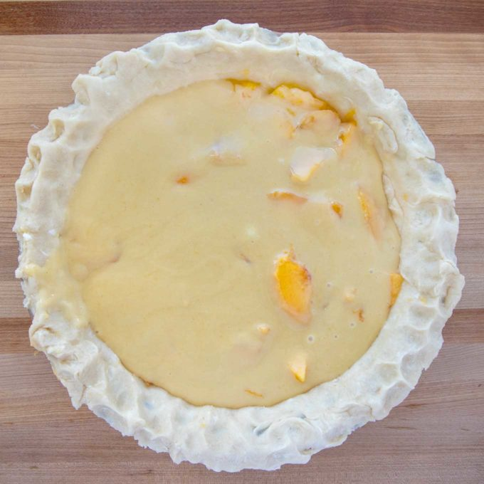 custard over the layer of peaches in an unbaked pie shell