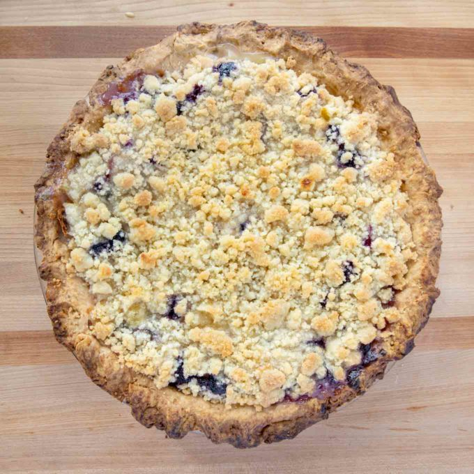 overhead view of a fully baked peach blueberry custard pie on a wooden cutting board