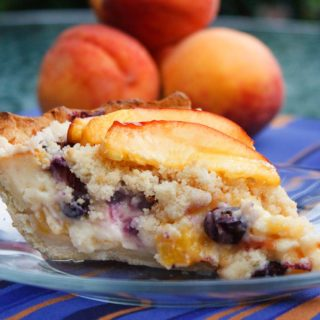 slice of peach blueberry custard pie on a glass plate with a stack of peaches behind it