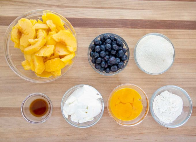 ingredients to make the filling for a peach blueberry custard pie in glass bowls