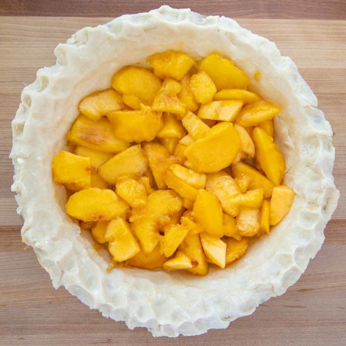 Pie crust in a glass pie pan with a layer of sliced peaches in the pie shell