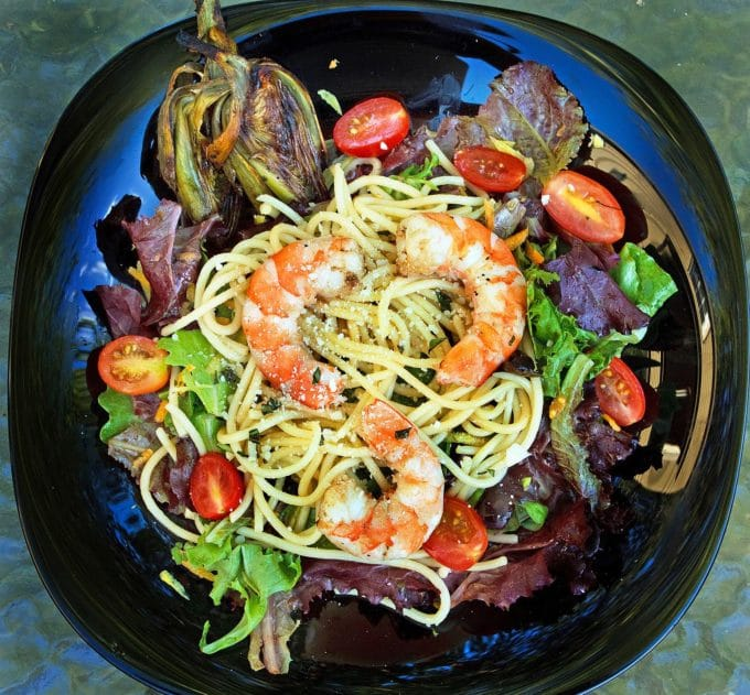 shrimp and spaghetti on top of a mixed green salad on a black plate