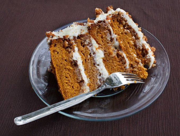 slice of four layer pumpkin crunch cake on a glass plate with a fork, sitting a brown table cloth