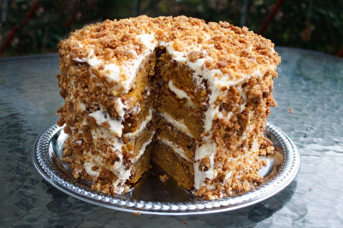 four layer pumpkin crunch cake with a slice cut out, sitting on a silver tray on a glass table