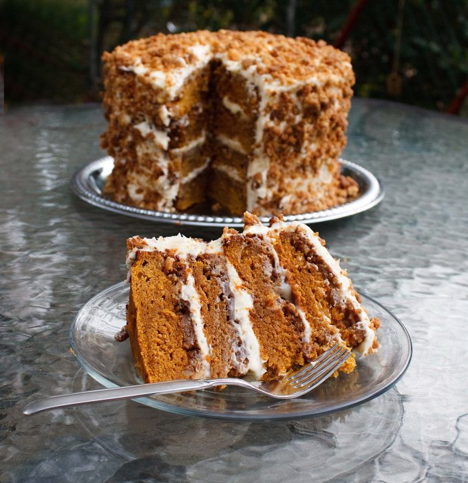 a slice of pumpkin crunch cake on a glass plate with a fork sitting on a large glass table sitting in front of a four layer pumpkin crunch cake