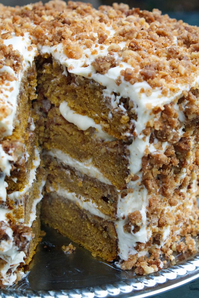 four layer pumpkin crunch cake with a slice taken out sitting on a silver tray