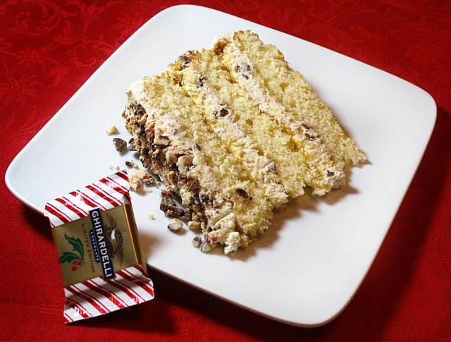 slice of a cannoli cream cake on a white plate with a Ghirardelli mint bark pack