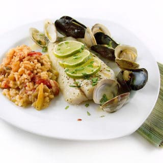 corvina topped with lime slices served with clams and mussels on a white plate with tomato risotto