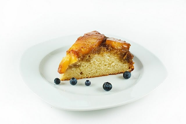 slice of Pineapple upside down cake on a white plate with blueberries