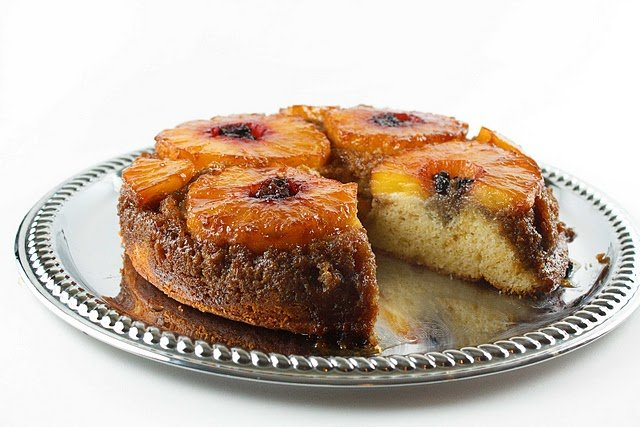 pineapple upside down cake with a slice missing on a silver platter