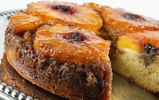view at an angle of a pineapple upside down cake with a slice missing on a silver platter