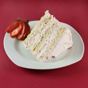 slice of strawberry cream cake on a white plate