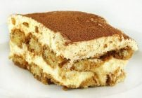 slice of tiramisu with a dusting of cocoa sitting on a white plate