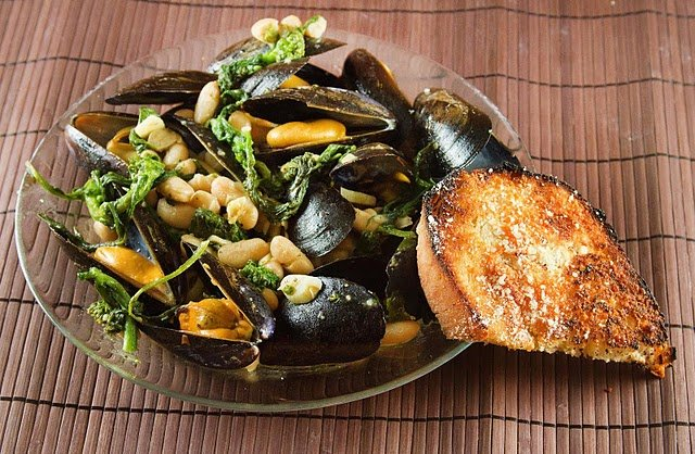 mussels with broccoli rabe and cannellini beans in a large glass bowl with a slice of garlic bread against the bowl