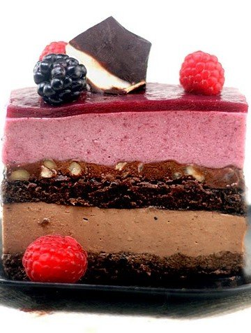 slice of entremet topped with berries on a black plate