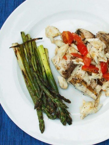 grilled mahi-mahi topped with crabmeat and grape tomatoes on a white plate with grilled asparagus