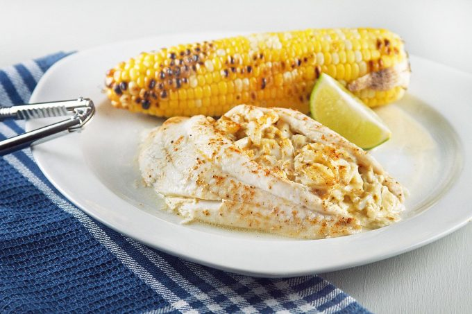 restaurant style stuffed flounder on a white plate with an ear of corn and lime slice sitting on a blue napkin