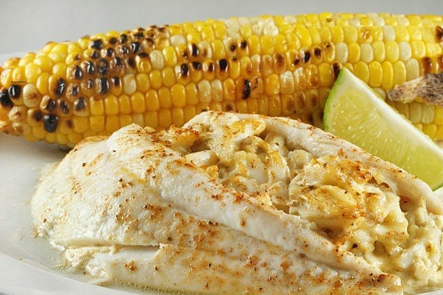 restaurant style stuffed flounder with a grilled ear of corn and a lime slice