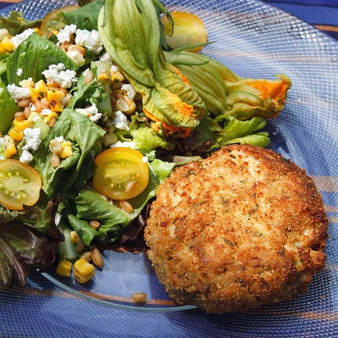 Famous Lump Crab cake on a glass plate with a salad on the side