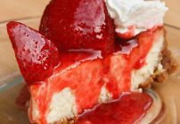 slice of mascarpone cheesecake topped with strawberries and strawberry sauce