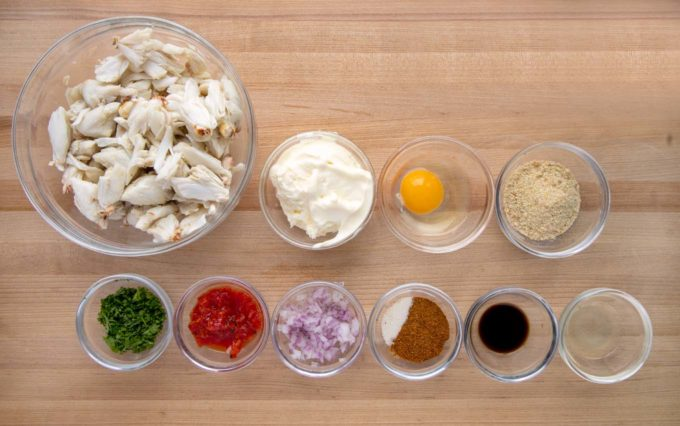 overhead view of ingredients ot make crabcakes in glass bowls on a wooden cutting board