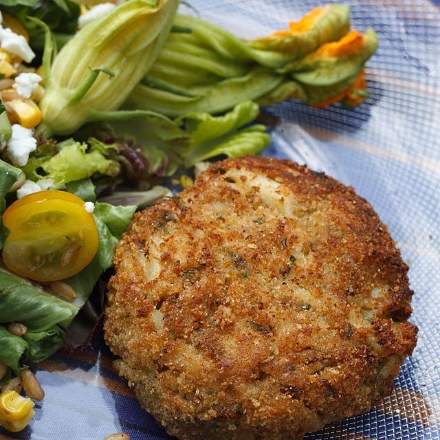 whole Crab cake sitting on a plate with a salad and garnished with a zucchini blossom