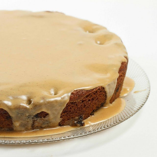 partial view of a whole blueberry molasses cake with a glaze