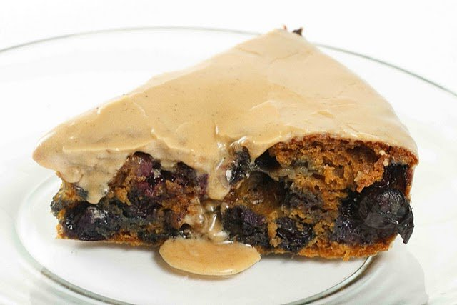 slice of blueberry molasses cake with a glaze on a white plate