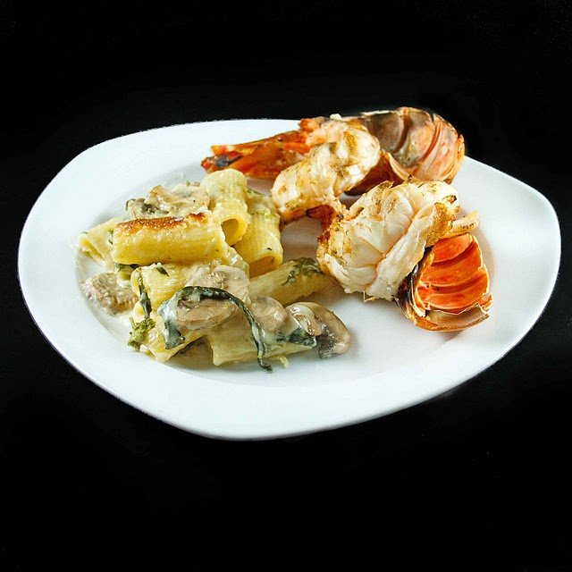 grilled lobster on a white plate  with broccoli rabe mac and cheese on the side