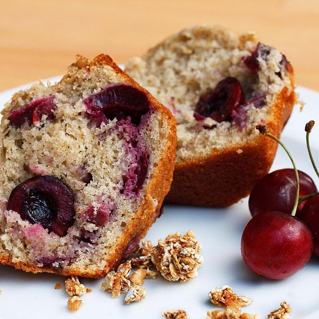 cherry vanilla muffin cut in half looking at both halves on a white plate with cherries