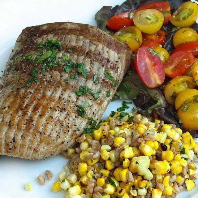 grilled Chesapeake bay ray next to corn mixture and sliced grape tomatoes