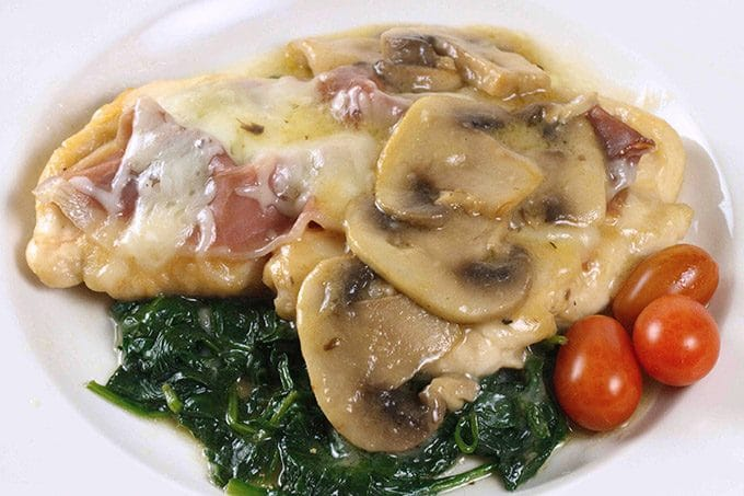 chicken saltimbocca on a white plate with a cherry tomato garnish