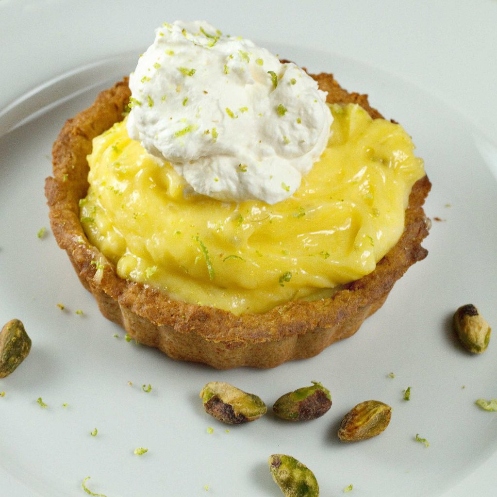 overhead view of a Key Lime Curd Tartlet topped with whipped cream on a white plate with pistachios