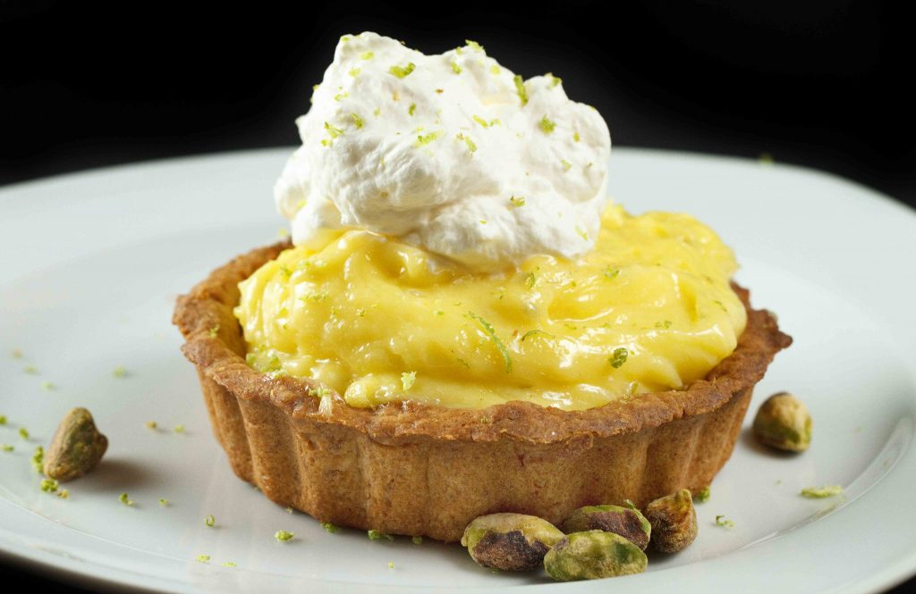 Key Lime Curd Tartlet with whipped cream and pistachios sitting on a white plate