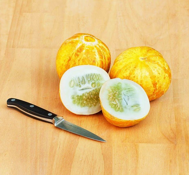 lemon cucumbers with one cut in half with a knife next to it