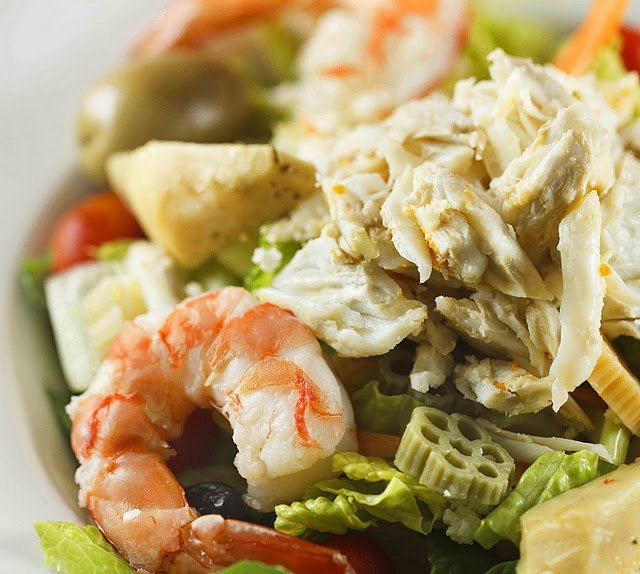 crabmeat and shrimp on top of a salad with pasta shapes
