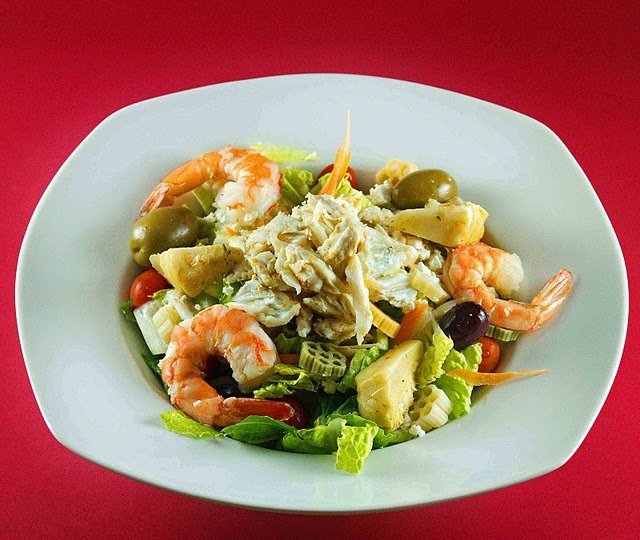 white bowl of mediterranean salad with shrimp and crabmeat on a red background