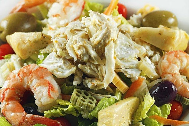 close up of crabmeat, shrimp, olives and artichokes on a bed of romaine