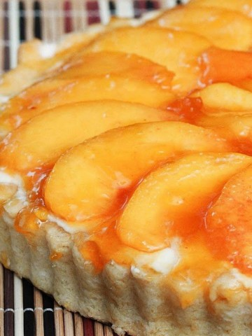 half view of a peach tart sitting on a placemat made out of multi colored wooden sticks