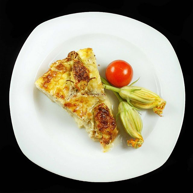 slice of strata and zucchini blossoms on a white plate