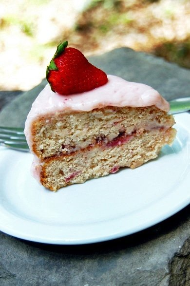 slice of strawberry cake with a whole strawberry on top of it