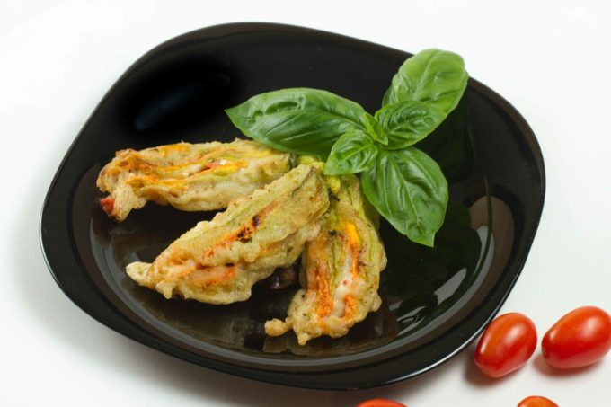 3 stuffed zucchini blossoms and a sprig of basil on a black plate next to grape tomatoes on a white table