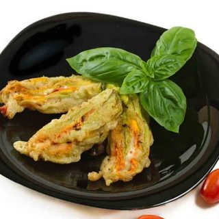 fried stuffed zucchini blossoms on a black plate with a sprig of  basil