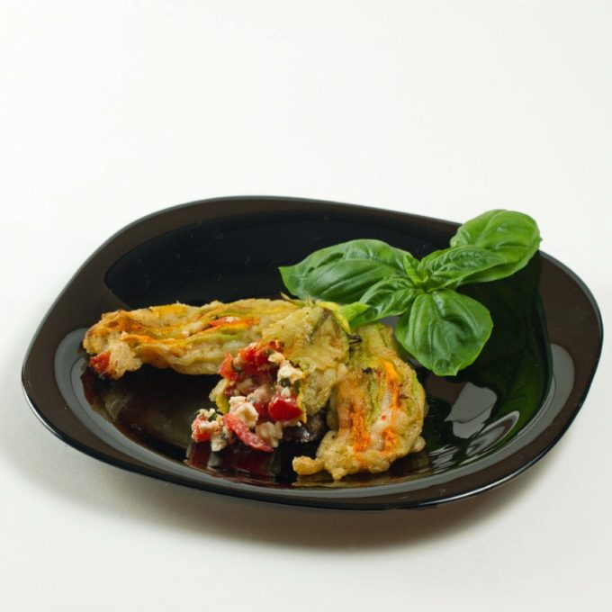 3 stuffed zucchini blossoms, one sith a bite out and a sprig of basil  on a black plate on a white background