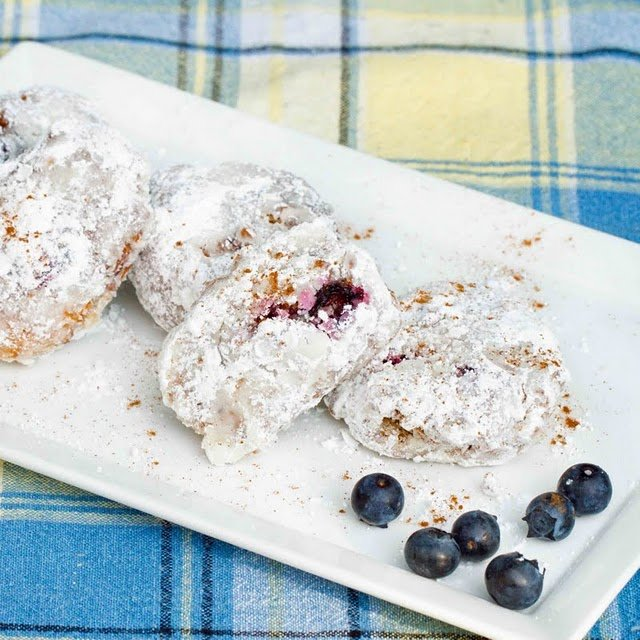 blueberry fritters coated in a powdered sugar sitting on a rectangular white platter with a few blueberris on a blue and yellow plaid tablecloth