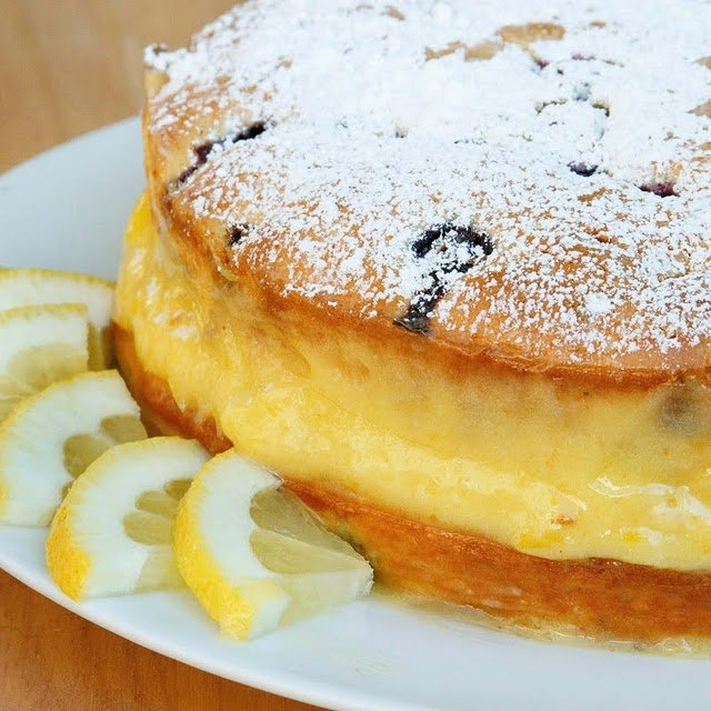 partial view of whole blueberry lemon cake on a white plattert