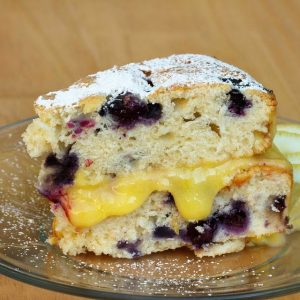 slice of blueberry lemon cake on a clear glass plate