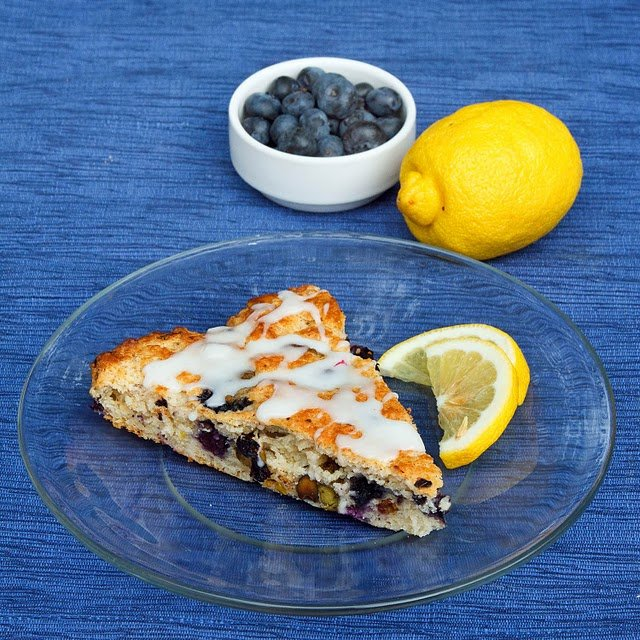 blueberry lemon scone on a clear plate with a bowl of blueberries and a lemon behind it